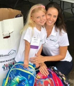 HomeAid Northern Virginia Executive Director Kristyn Burr and her daughter hand out backpacks at the 2016 Night at the Ballpark.